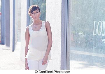 Beautiful brunette model walking on street beige blouse...