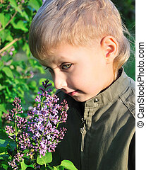Boy With Lilac for mother - Little blond boy is standing...