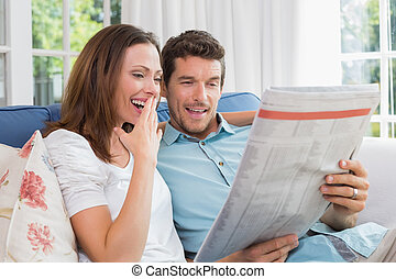 Happy couple reading newspaper on couch - Happy young couple...