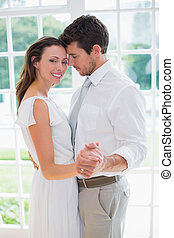 Loving young couple holding hands at home - Side view of a...