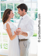 Loving young couple holding hands - Side view of a loving...
