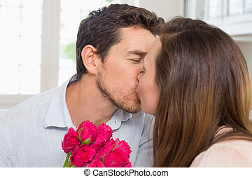 Close-up of a loving couple kissing with flowers - Close-up...