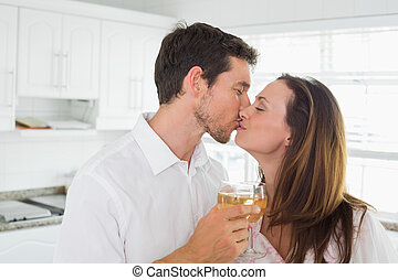 Loving couple kissing with wine glass in hand in kitchen -...