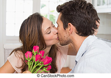 Loving couple kissing with flowers in hand at home - Side...