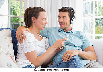 Couple listening music with mobile phone on couch - Relaxed...