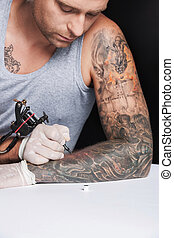 young tattooist drawing picture on hand. young man looking...