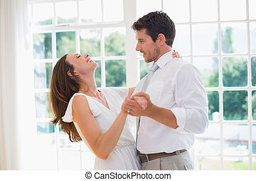 Loving young couple dancing at home - Side view of a loving...