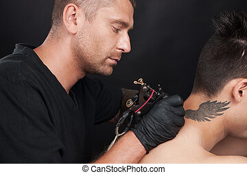 professional tattooist drawing on man neck. tattooer drawing...