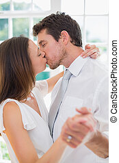 Loving young couple kissing at home - Side view of a loving...