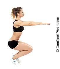 Athletic woman doing squats - Studio shot of an athletic...
