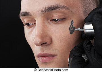 handsome young face getting tattoo. professional tattooist...