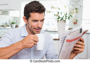 Man drinking coffee while reading newspaper at home -...