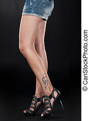 beautiful girl legs with tattoo symbol. young woman feet standing on black