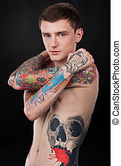 handsome young man with colorful tattoo. tattoo covered guy...