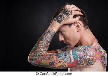 man with tattoo holding head with hands young male with...