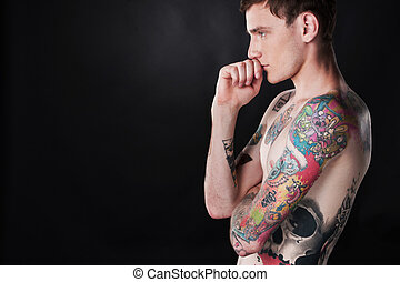 handsome young man covered with tattoo. sexy male with...