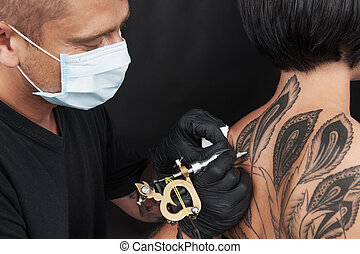 professional tattooist making back tattoo young girl...