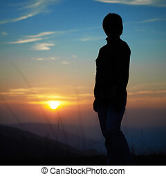 Silhouette of woman against sunset