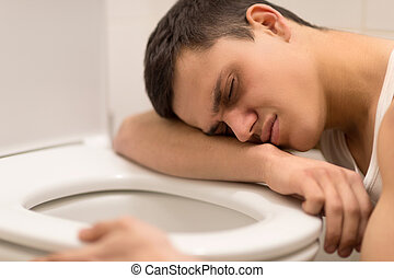 young man lying on toilet seat. drunk man kneeling over...