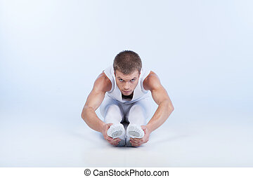 ballet dancer sitting on floor and stretching. handsome male...