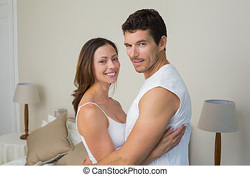 Happy couple with arms around at home - Portrait of a happy...