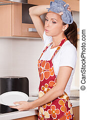 Beautiful young brunette washing dishes tired and exhausted...