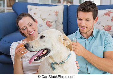 Relaxed couple with wine glasses and pet dog in living room