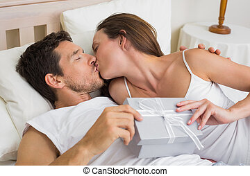 Couple kissing with gift box in hand in bed - Relaxed young...