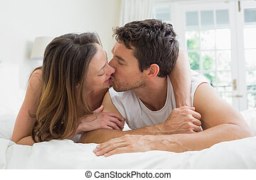 Relaxed couple kissing in bed - Relaxed young couple kissing...