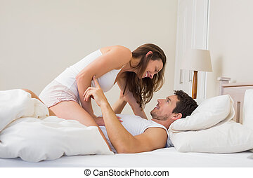 Young woman sitting on man in bed - Side view of a young...