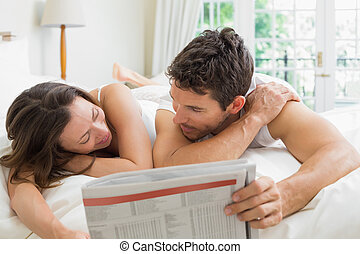 Relaxed couple reading newspaper in bed - Relaxed young...