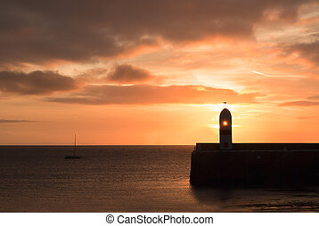 Lighthouse on breakwater wall with calm sea during sunrise -...
