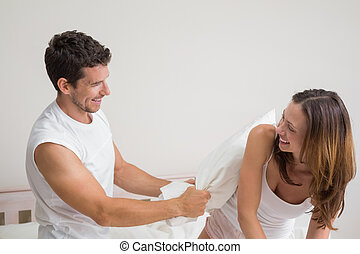 Cheerful couple pillow fighting in bed - Cheerful young...