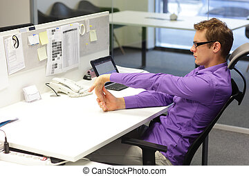execises in office - man exercising during work with tablet...