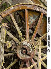 old wooden cartwheel against wood cart - Old wooden...