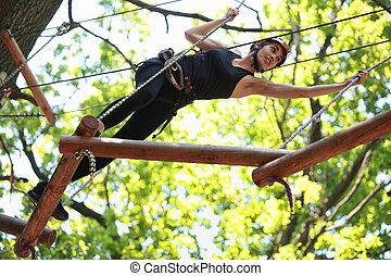 climbing in adventure rope park - Young atractive woman...