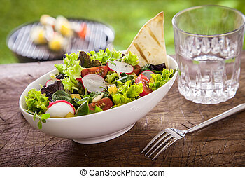 Healthy summer salad with a glass of fresh water
