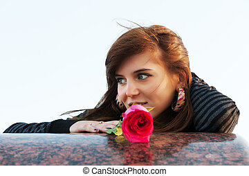Happy young woman with a red rose