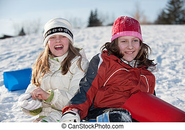 girls playing on hill - girls resting on the tobogganing...