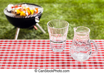 Glass of fresh water with a jug on a picnic table covered...