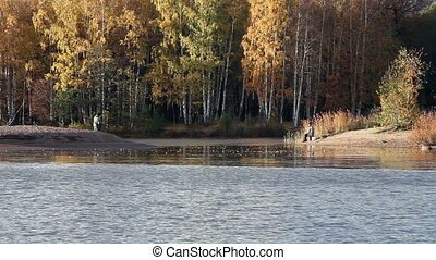 Fishermen on the lake shore in autu - view of the lake...