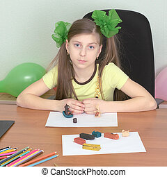 Girl sitting at a table with plasticine in hands