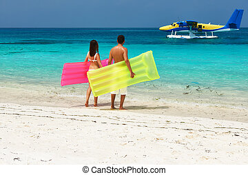 Couple with inflatable rafts looking at seaplane on beach -...