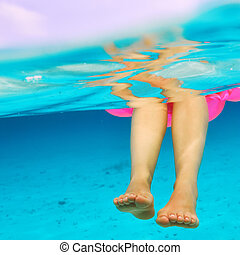 Woman relaxing on inflatable mattress, view from underwater...