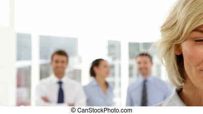 Businesswoman standing in front of her team in the office