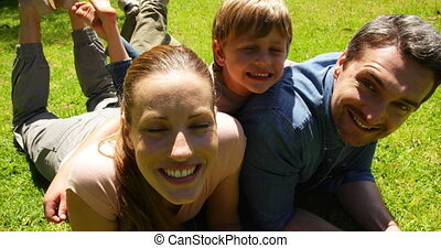 Little boy and parents smiling in the park on a sunny day