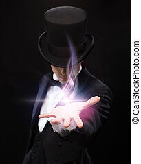 magician holding something on palm of his hand - magic,...