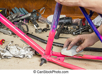 Hands of real bicycle mechanic sanding frame bike - Hands of...