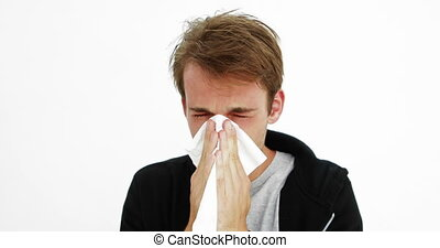 Sick young man blowing his nose on white background
