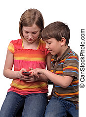 kids texting - Two young kids texting messages on a smart...